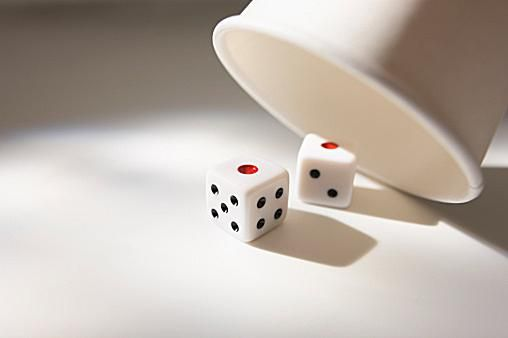 Two dice showing one lying beside dice cup