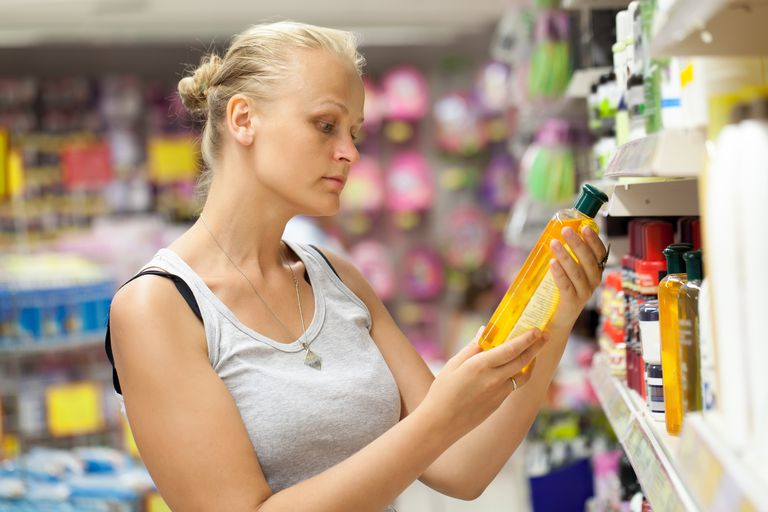 Young Woman Looking At Product While Buying From Supermarket