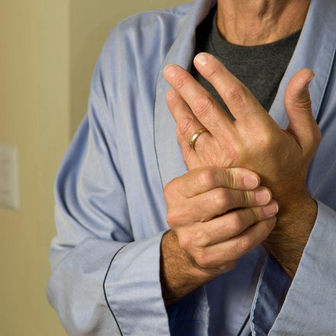 man rubbing painful hand