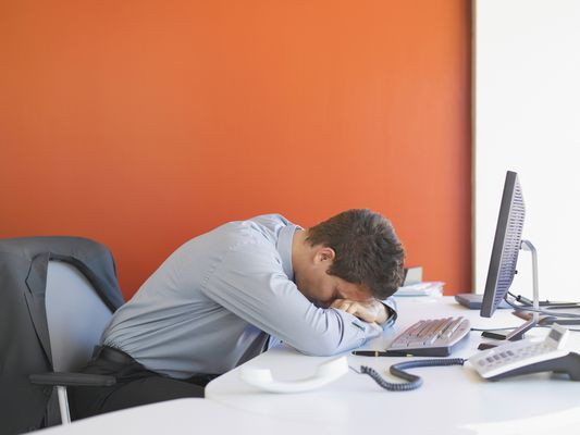 Business man leaning head on desk in office
