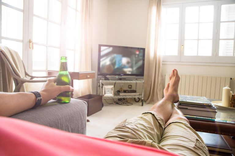 Man watching tv with a beer