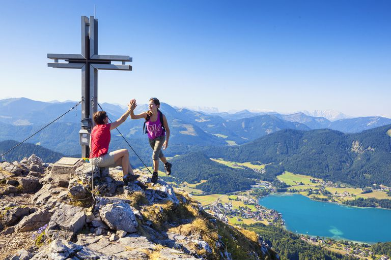 Austria, Salzburg, Salzburg District, Fuschl am See, Schober, Mother and daughter giving high-five and enjoying vacation