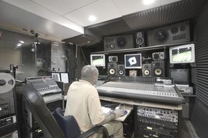 Sound director recording and mixing music in studio, rear view