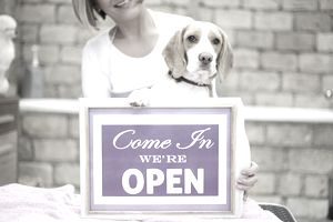 human and her dog holding a sig that says Come In We're open