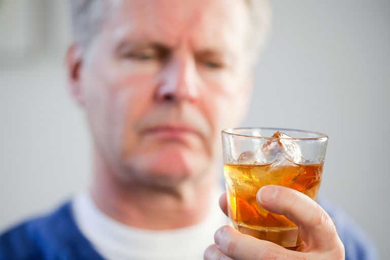 senior man looking at glass of whiskey