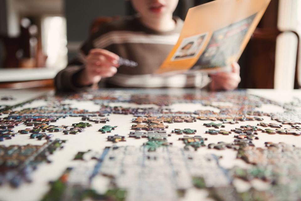 Young boy finishing puzzle