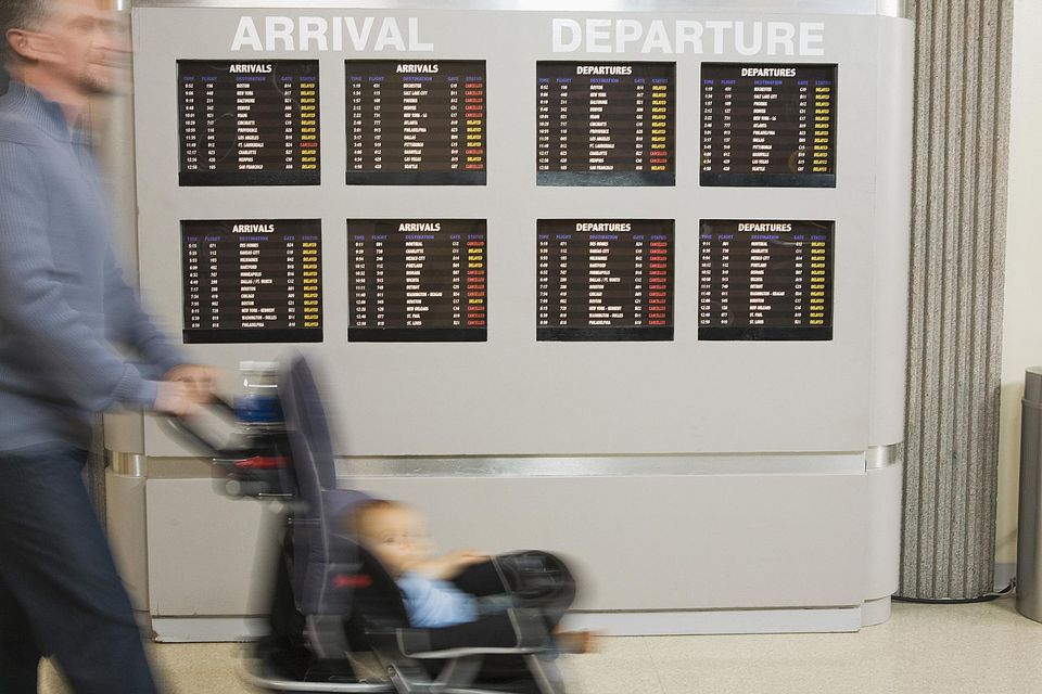 Side view of man walking by flight information at airport