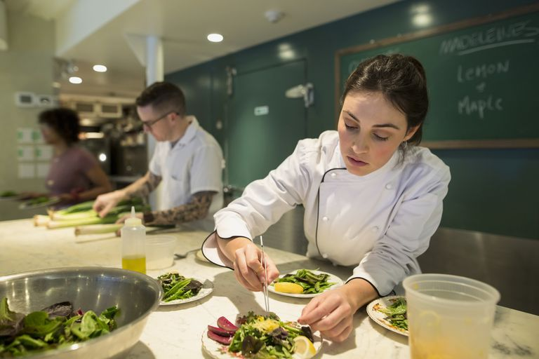 Focused female chef plating salad tweezers restaurant kitchen