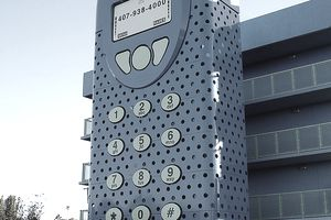 giant cell phone sculpture outside of a building