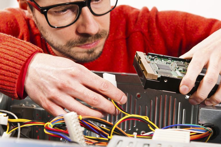 Photo of a man fixing a desktop computer
