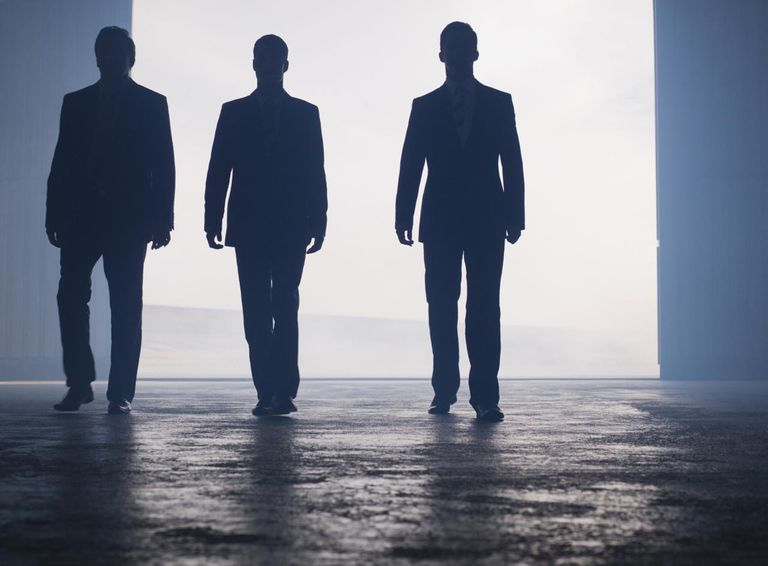 Silhouettes of businessmen walking