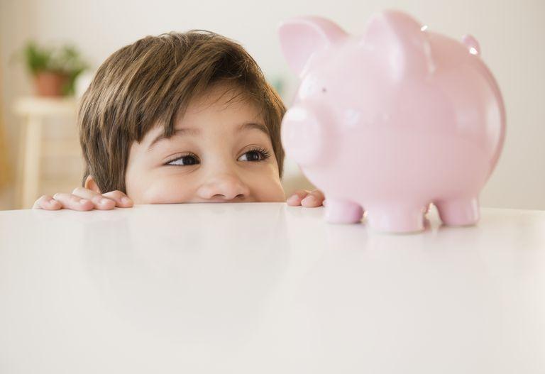 Hispanic boy examining piggy bank