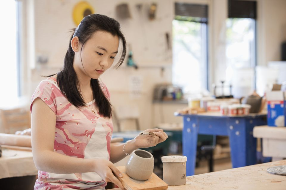 Young girl glazing pottery