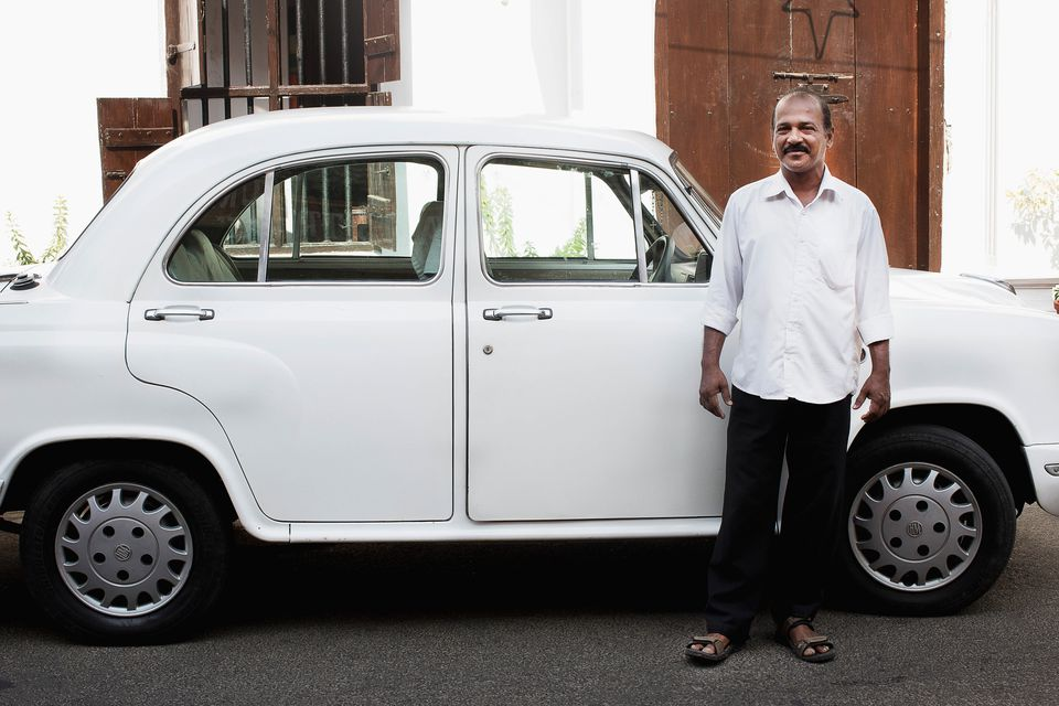 White Ambassador taxi car and driver.