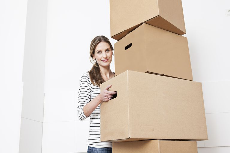 Woman carrying stack of cardboard boxes, smiling