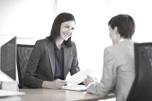 Two women smiling and talking over a desk about a piece of paper in their hands
