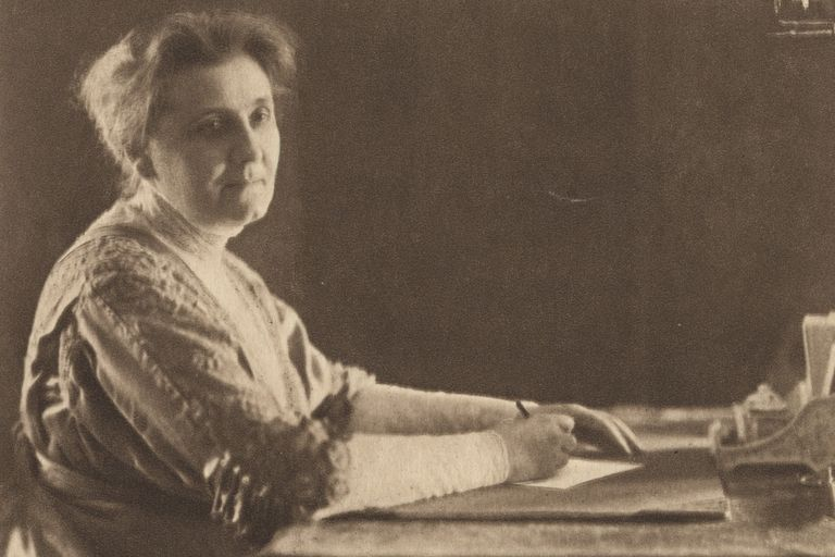 Jane Addams writing a letter at her desk