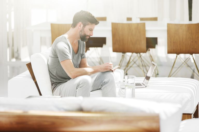 Man writing in notebook on white couch