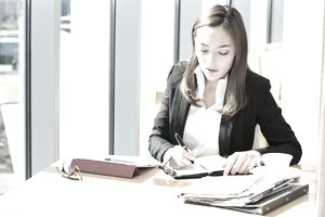 Businesswoman writing something on a note