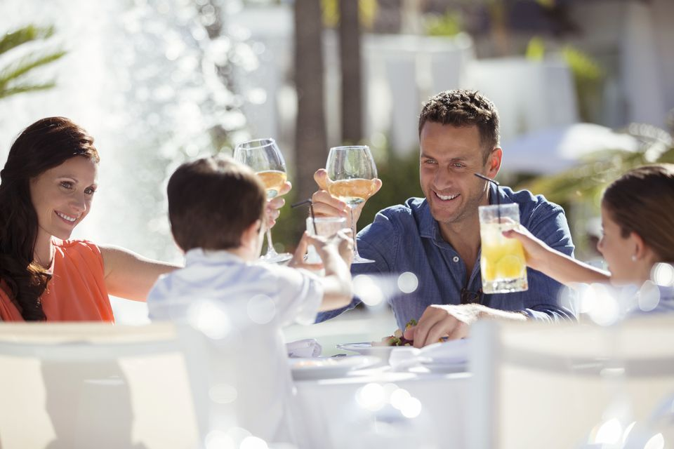 Family with two children raising toast at table outdoors
