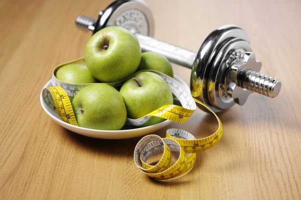Apple, dumb bell and measuring tape
