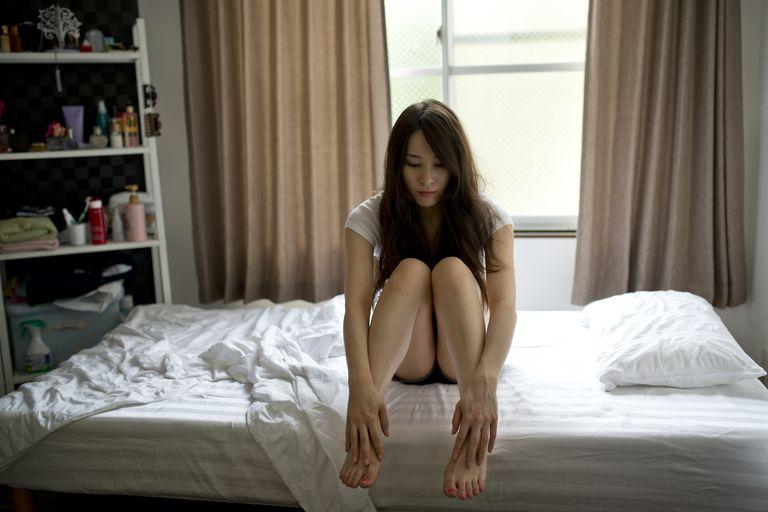 girl sitting pensively holding her legs in bedroom.