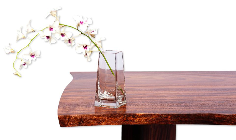 A glass vase with an orchid sits on a modern wooden table