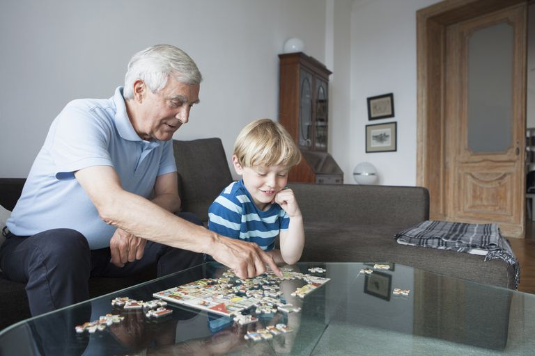 Grandfather solving jigsaw puzzle with grandson in living room at home