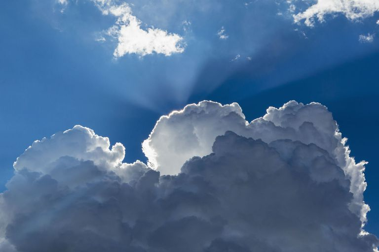 Sunbeams shining through clouds in blue sky