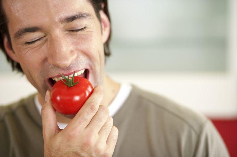 Man eating a tomato