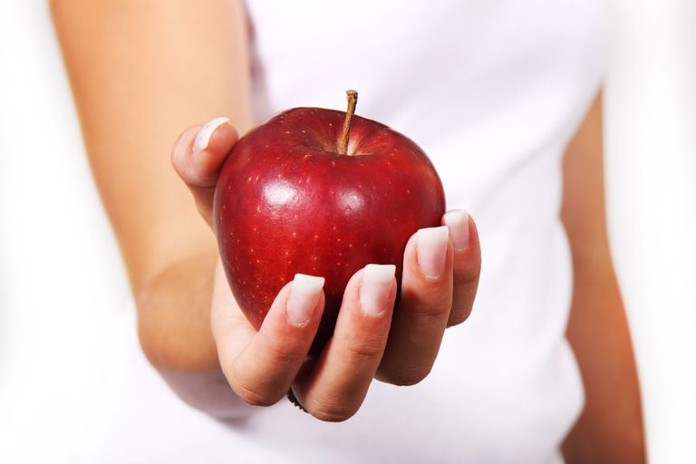 woman's hand holding an apple