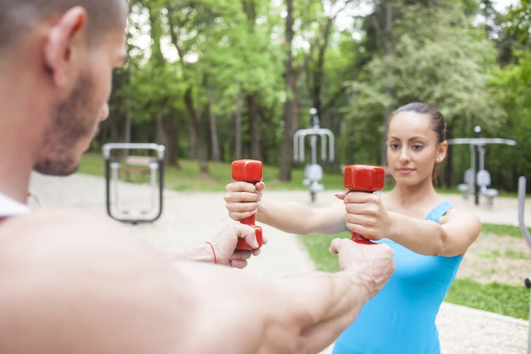 Woman holding weights with trainer