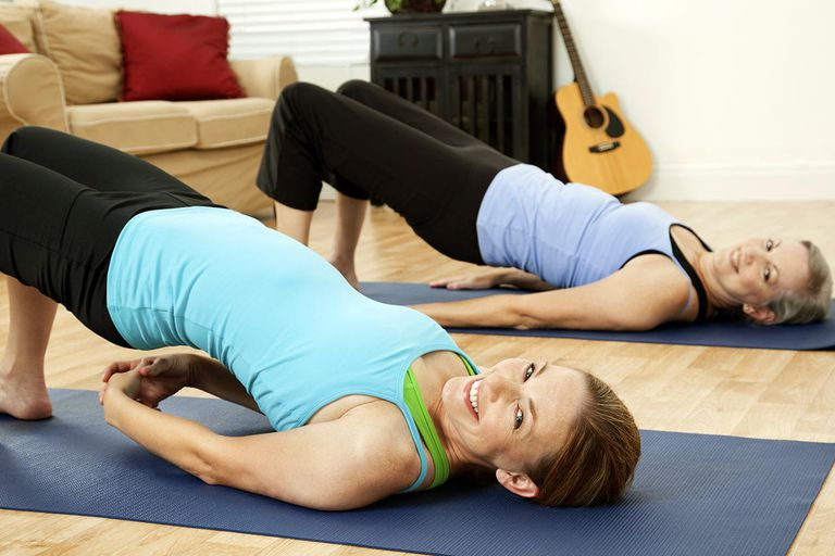 Women in Home Stretching back on exercise mats. See more from this series: