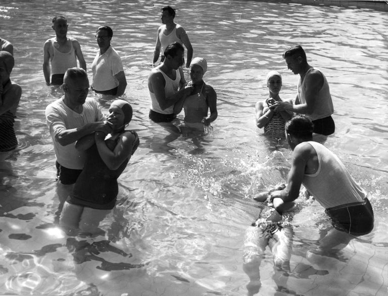 circa 1960: Jehovah's Witnesses being baptised by complete immersion.