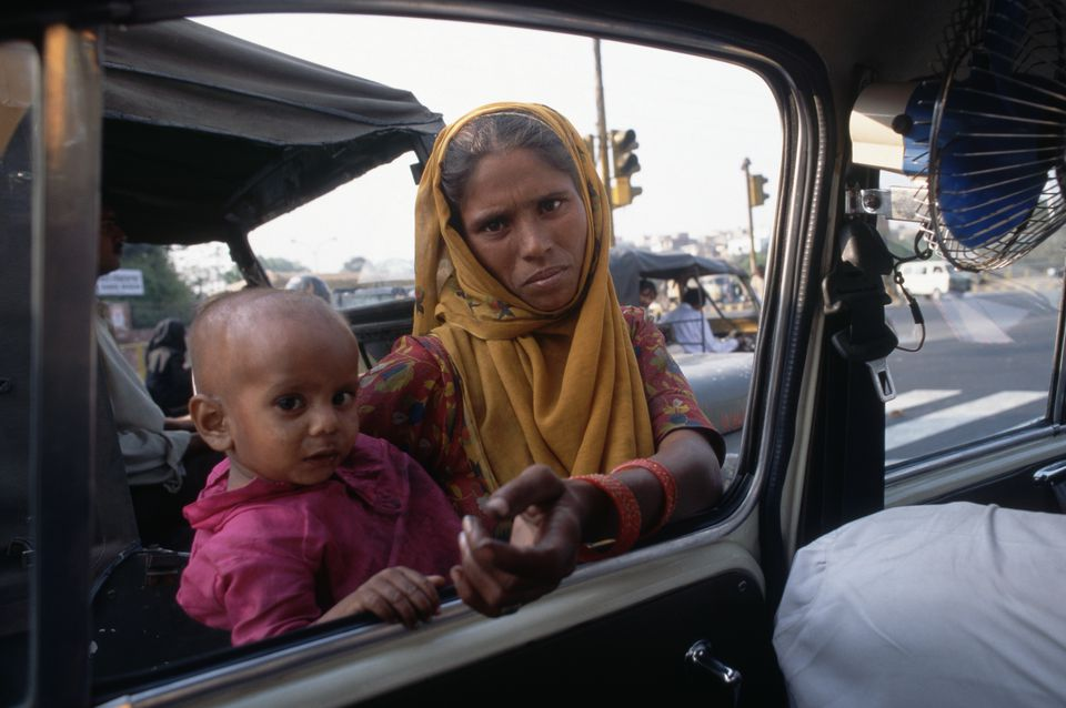 A woman carrying a young child begs for money outside a taxicab in New Delhi.
