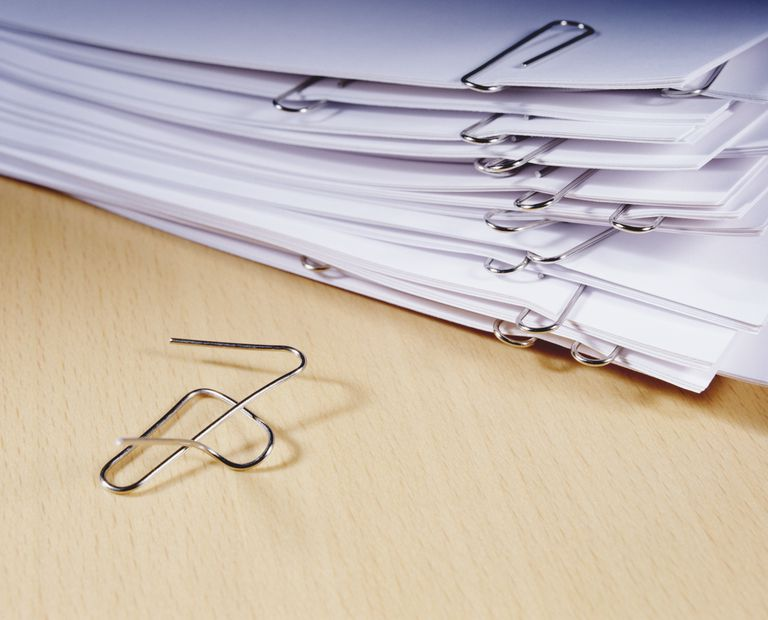 Stack of printing paper held in bunches by paper clips