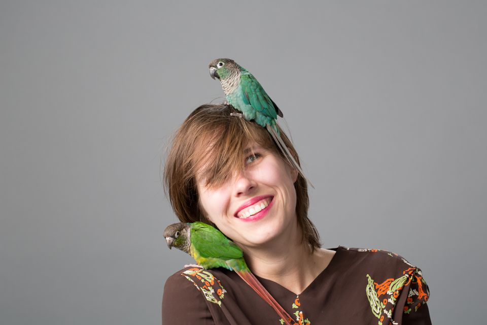 Woman with two Green-cheeked Parakeets