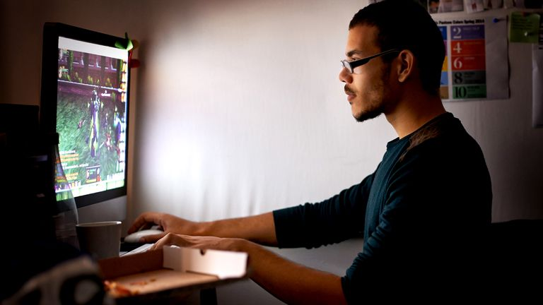 Man wearing glasses playing a video game on his PC in a dark room