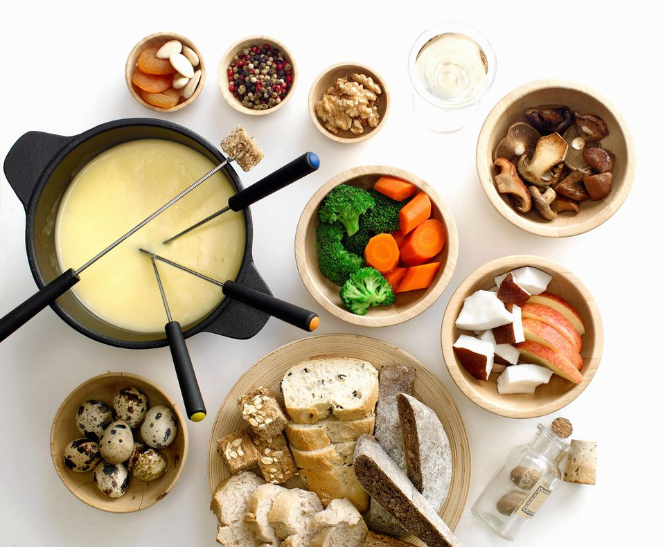 Bowls of cheese fondue with vegetables, mushrooms, bread