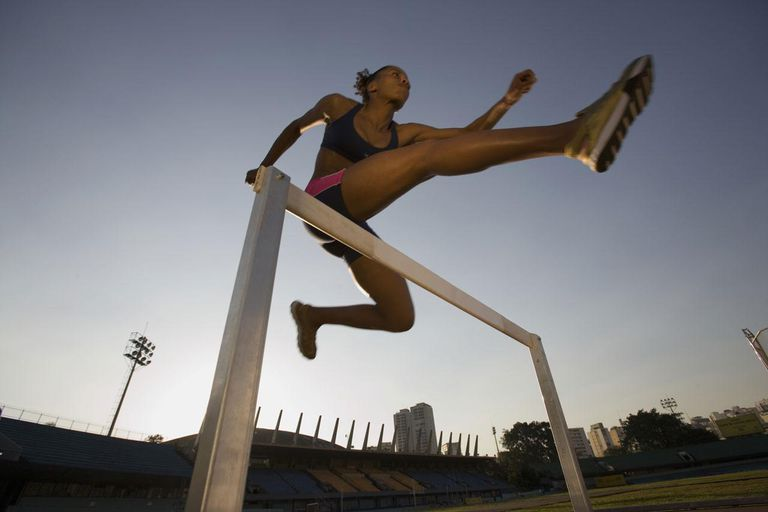 Female athlete clearing hurdle, low angle view, sunset