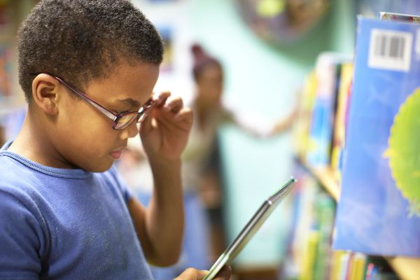 Boy with glasses reading from E-reader
