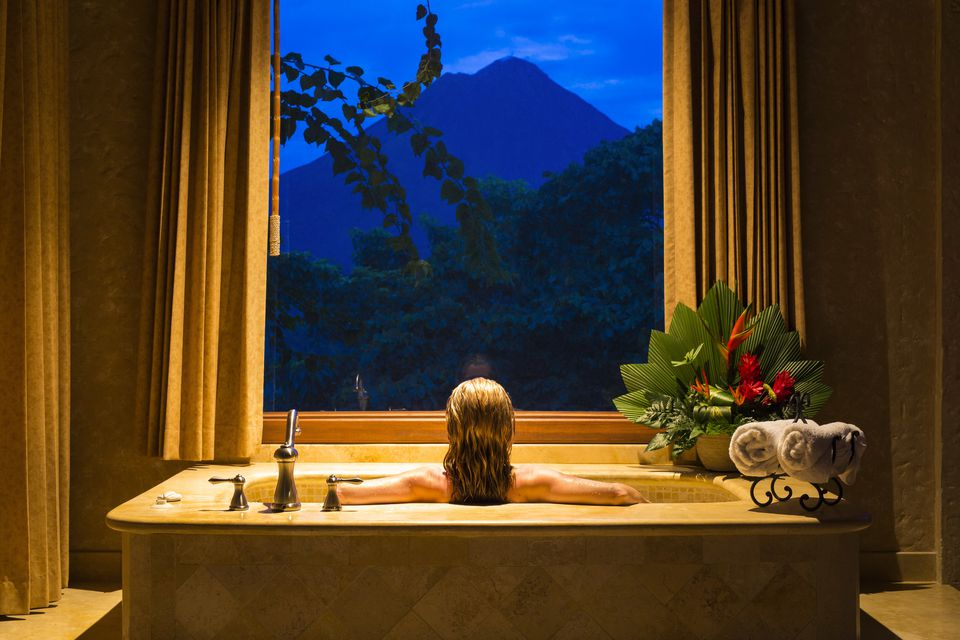 Costa Rica, Alajuela, La Fortuna. A lady looks out at the Arenal Volcano from a suite in the The Springs Resort and Spa. .