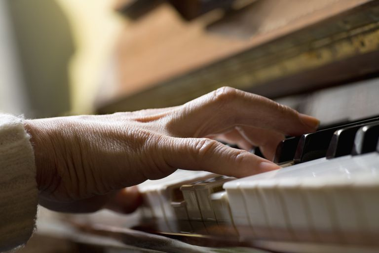 Piano chord being played by woman's hand