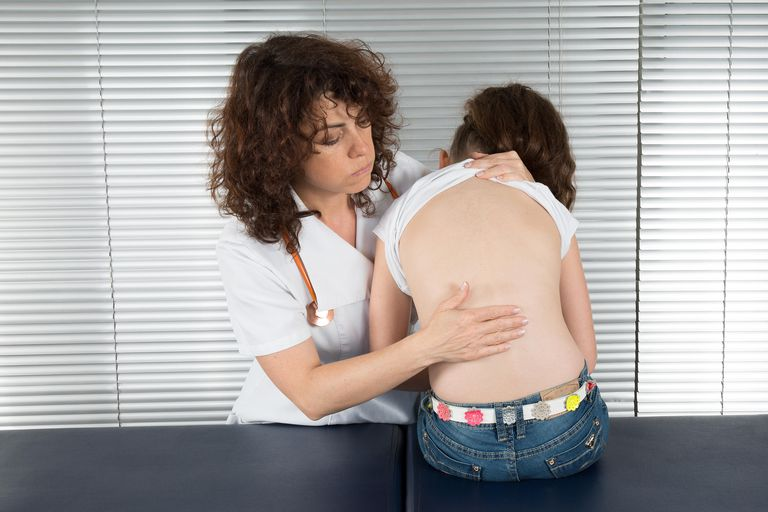 A doctor examines a young patient's spine.