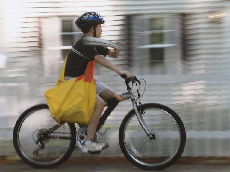 Newspaper delivery boy riding bike