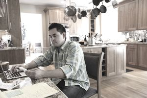 man doing taxes in kitchen