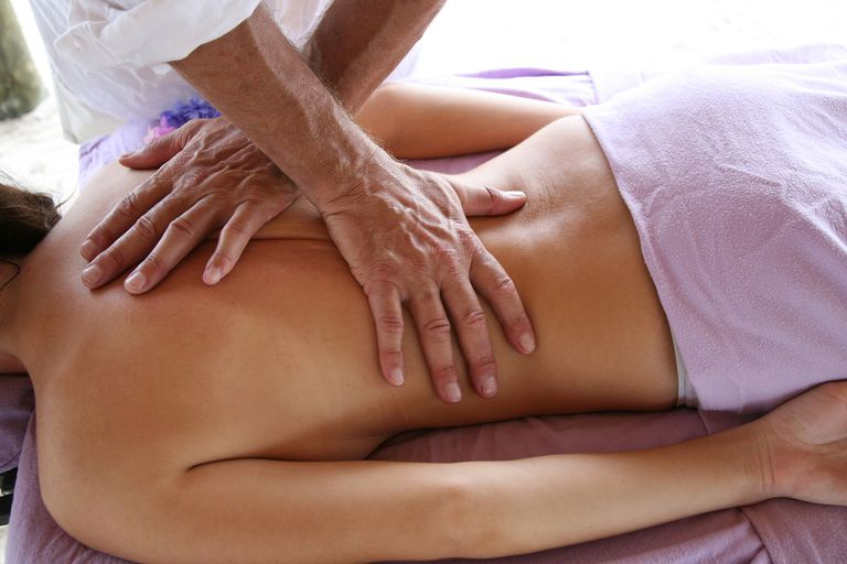 Woman receiving low back massage.