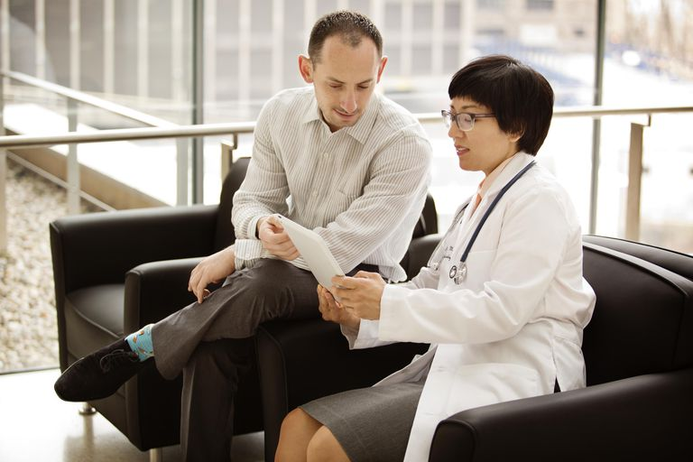 Female doctor sitting with male fertility patient, getting instructions for semen analysis
