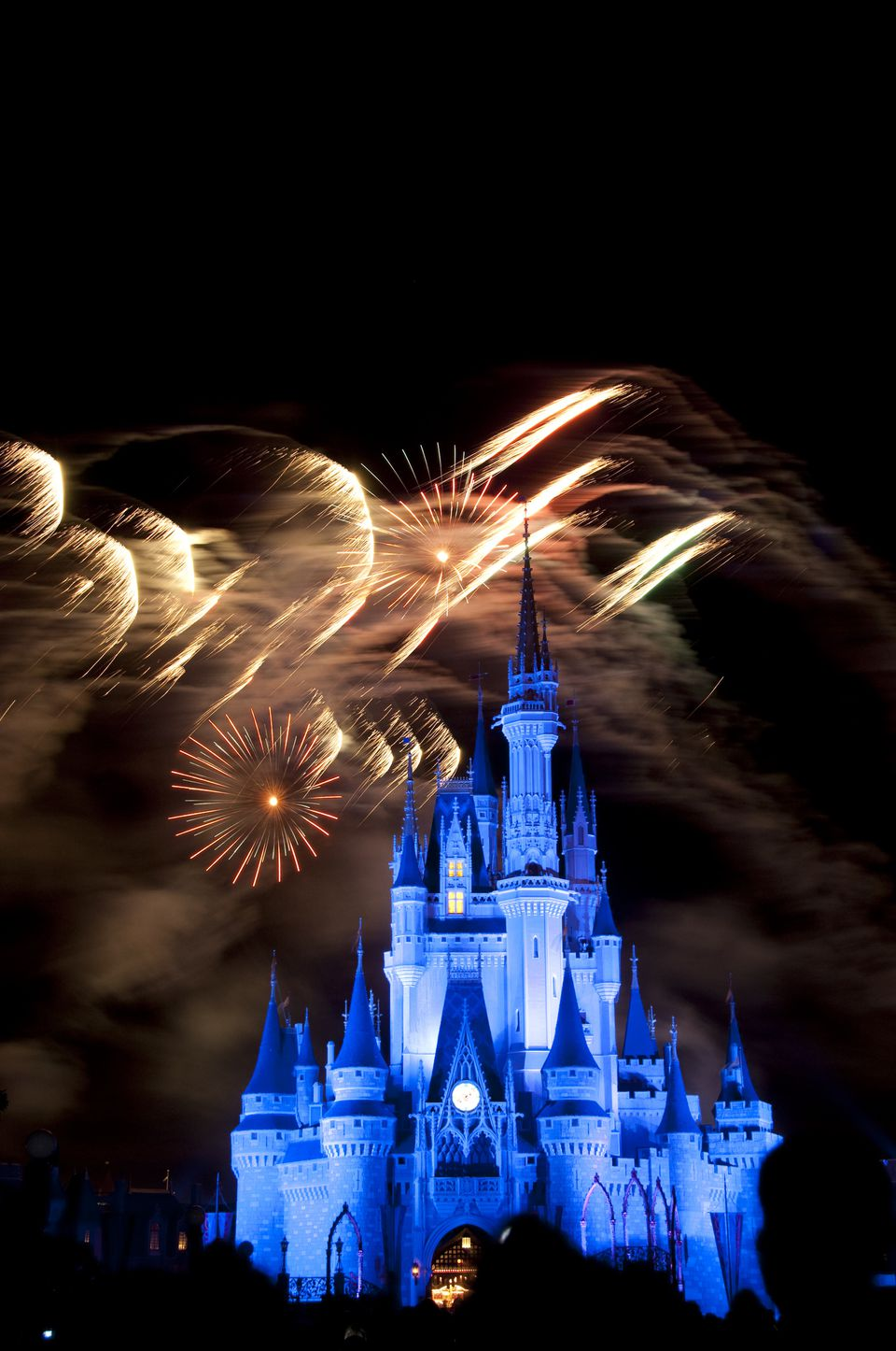 Crowds and Magic Kingdom castle during nightly fireworks, Disney World.
