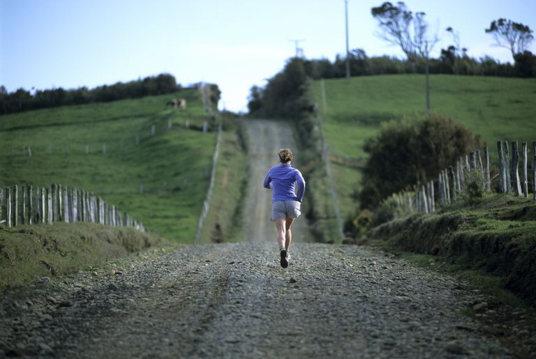 A woman runs along a deserted country road, Chile.